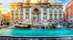 Tourists throw coins in Rome's Trevi fountain for good luck