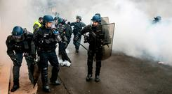 French riot police take position in a cloud of tear gas during clashes with yellow vest protesters in Lyon. Photo: AP Photo/Laurent Cipriani