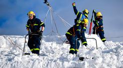 Dig: Rescue workers clear a roof following snowfall in Kruen, Germany. Photo: Philipp Guelland/Getty Images