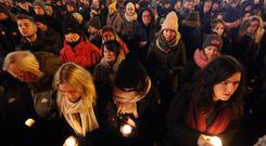 People hold lit candles in a memorial march for Gdansk Mayor Pawel Adamowicz, in Warsaw, Poland, Monday, Jan. 14, 2019. People in Poland are gathering for solemn vigils to honor Gdansk Mayor, 53-year-old Pawel Adamowicz. who died Monday after being stabbed at a fundraising event the night before. There were vigils in Warsaw and other cities across a nation shocked by the assassination. (AP Photo/Czarek Sokolowski)