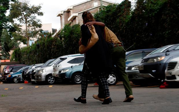 A woman is helped at the scene where explosions and gunshots were heard at the Dusit hotel compound, in Nairobi, Kenya January 15, 2019. REUTERS/Thomas Mukoya