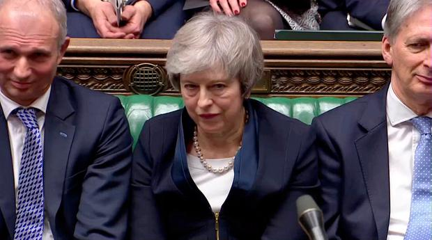 Theresa May sits down in Parliament after the vote on her Brexit deal.