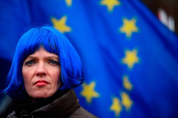 Protest: A woman stands in front of an EU flag outside the Houses of Parliament in central London yesterday. Photo: Getty