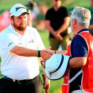 Shane Lowry of Ireland shakes hands with caddie Brian