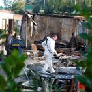 Aftermath: Garda forensic teams examine the scene of the fatal blaze. Photo: Collins photos