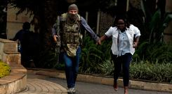An off-duty SAS soldier leads a woman to safety after the Nairobi attack. Photo: Reuters