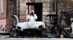 A forensic officer takes a photograph of the scene of a suspected car bomb in Derry, January 20, 2019. REUTERS/Clodagh Kilcoyne