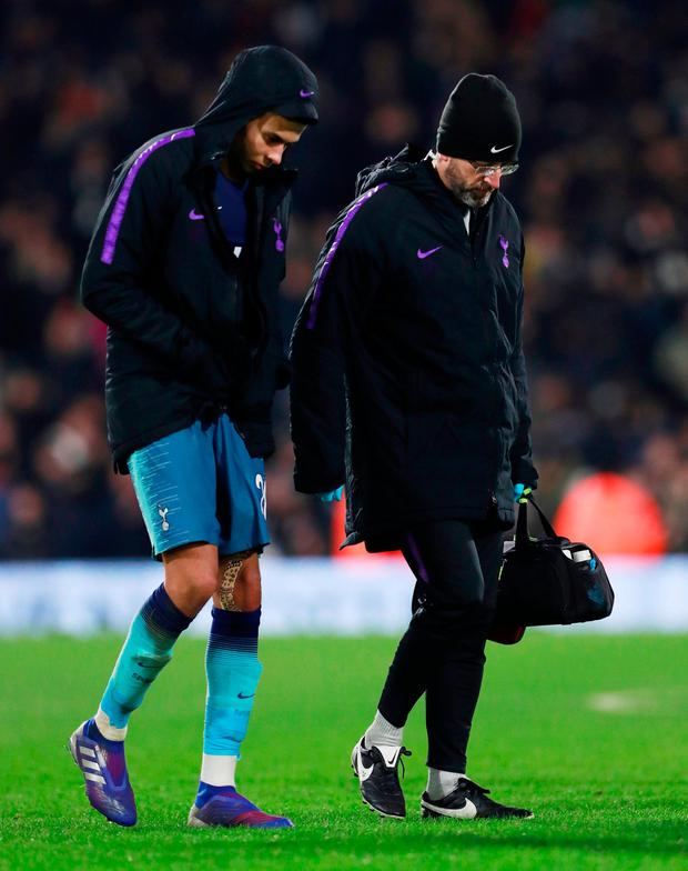 Tottenham's Dele Alli walks off the pitch with the physio at the end of the match