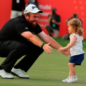 Shane Lowry celebrates his victory at the Abu Dhabi Championship with his daughter Iris and wife Wendy on the 18th green. Photo: Getty Images