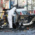 Forensic experts examine the remains of the car that exploded outside Derry courthouse. Photo: Margaret McLaughlin
