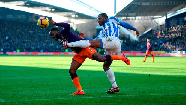 Raheem Sterling of Manchester City is tackled by Jason Puncheon of Huddersfield. Photo by Gareth Copley/Getty Images