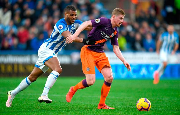 Steve Mounie of Huddersfield chases down Kevin De Bruyne of Manchester City. Photo by Gareth Copley/Getty Images