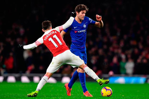 BARRIER: Marcos Alonso is tackled by Lucas Torreira. Pic: Getty Images