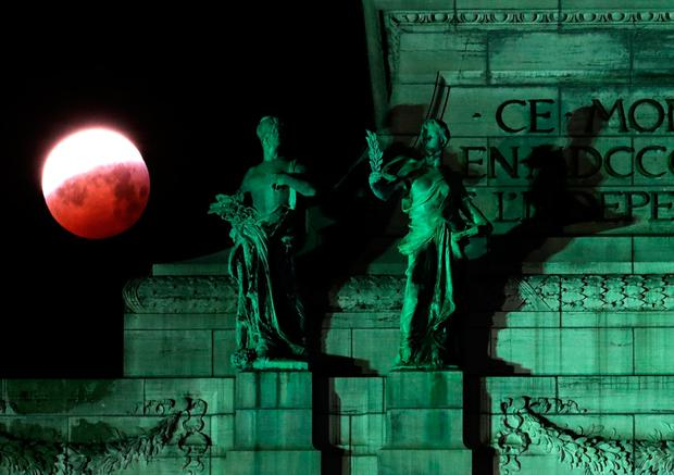 The moon is seen beside statues on top of the Cinquantenaire arch during a total lunar eclipse, known as the