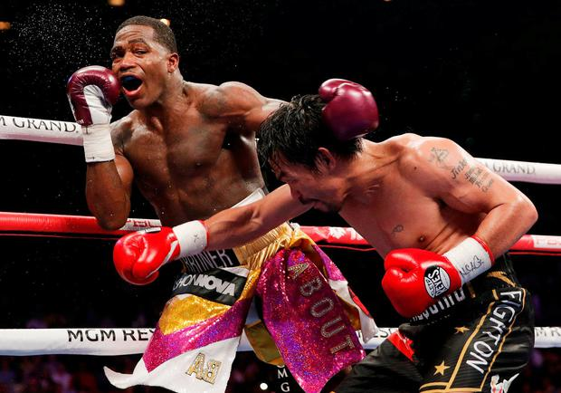Manny Pacquiao, right, hits Adrien Broner during a WBA welterweight title boxing match Saturday in Las Vegas. (AP Photo/John Locher)