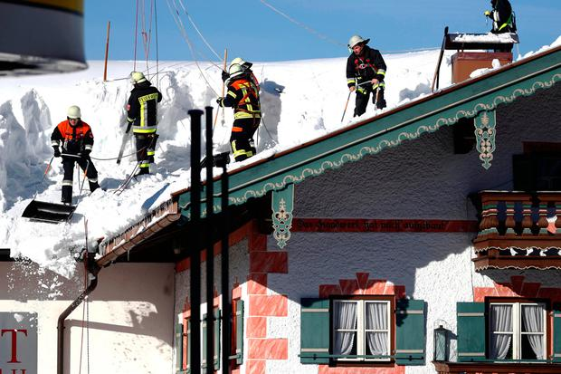 Workers clear snow from a house in Germany. AP Photo/Matthias Schrader