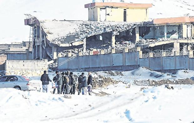 Attack: Afghan men stand in front of a collapsed building of the military base in Maidan Wardak yesterday. Photo: Reuters