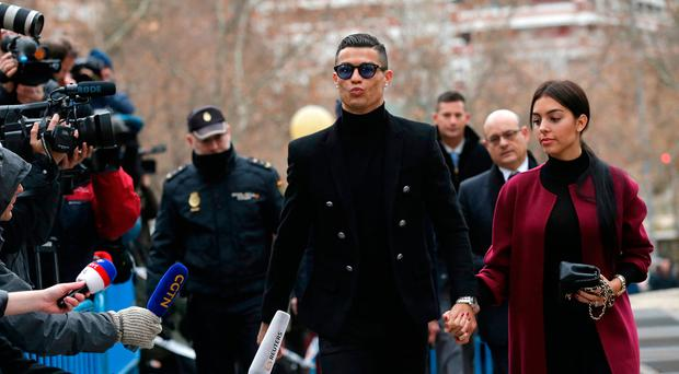Cristiano Ronaldo arrives at the court in Madrid on Tuesday, Jan. 22, 2019. Cristiano Ronaldo is expected to plead guilty to tax fraud. The Juventus forward arrived in a black van, walked up some stairs leading to the court house and stopped to sign an autograph. The charges stem from his days at Real Madrid. (AP Photo/Manu Fernandez)