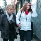 Friend of the Connors family Lisa Algan, left, and Maggie Connors, sister of Thomas Connors, leave the Coroner's Court on Store Street, Dublin, yesterday.