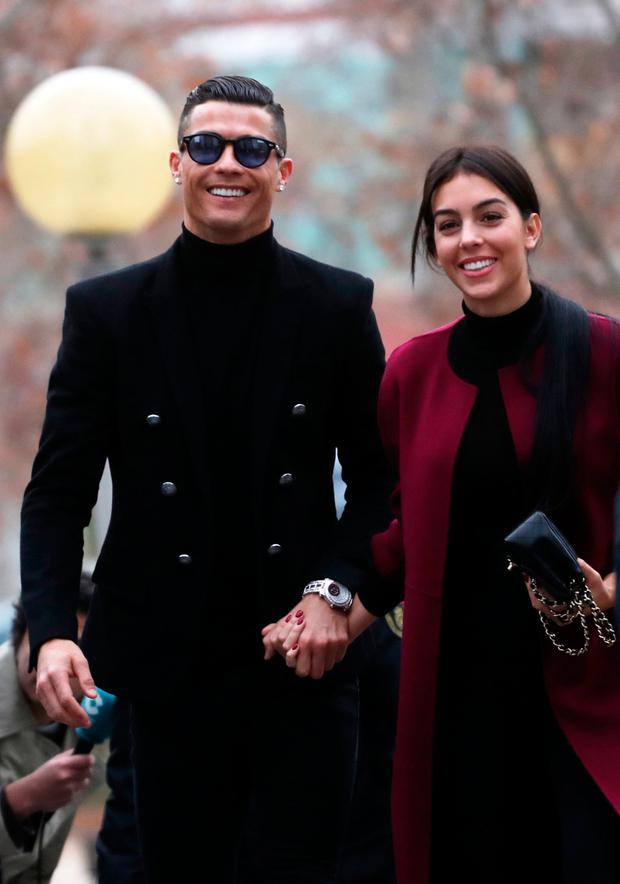 Brave face: Cristiano Ronaldo arrives at court in Madrid with his girlfriend Georgina Rodriguez. Photo: Susana Vera