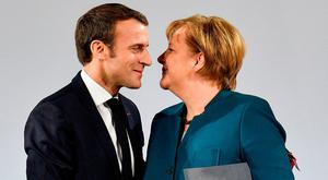 Friendly alliance: Emmanuel Macron and Angela Merkel embrace after signing the new Franco-German accord yesterday. AP Photo/Martin Meissner