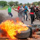 Flashpoint: Protesters stand behind a burning barricade during protests on a road leading to Harare, Zimbabwe. REUTERS/Philimon Bulawayo