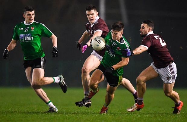 QUB's James McCauley breaks through a tackle from Stephen Brennan, right, and Cein Darcy. Photo: David Fitzgerald/Sportsfile