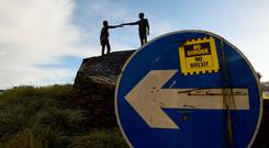 Statement: A 'No Border, No Brexit' sticker is seen on a road sign in front of the Peace statue entitled 'Hands Across the Divide' in Derry. Photo: Reuters