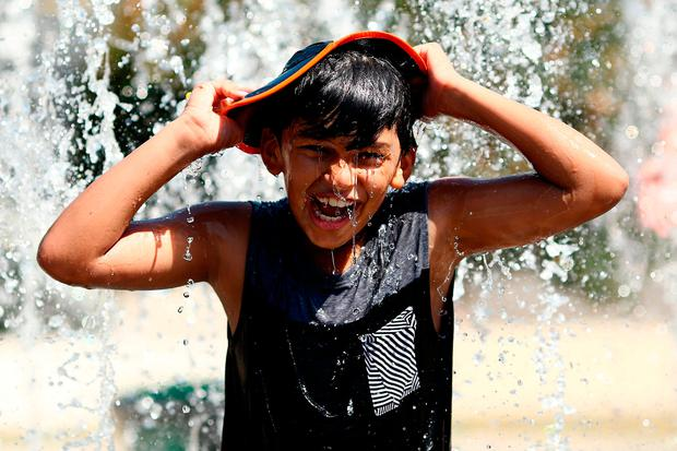 A young fan cools off a fountain in the hot conditions during day 11 of the 2019 Australian Open at Melbourne Park on January 24, 2019 in Melbourne, Australia. (Photo by Matt King/Getty Images)