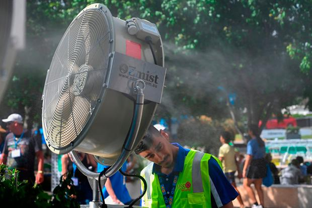 A man cools down in front of a mist fan on day 12 of the Australian Open tennis tournament in Melbourne on January 25, 2019.SAEED KHAN/AFP/Getty Images