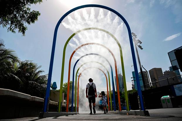 A man and a child walk through a mist tunnel to cool off on day 12 of the Australian Open tennis tournament in Melbourne on January 25, 2019. (Photo by Saeed KHAN / AFP)