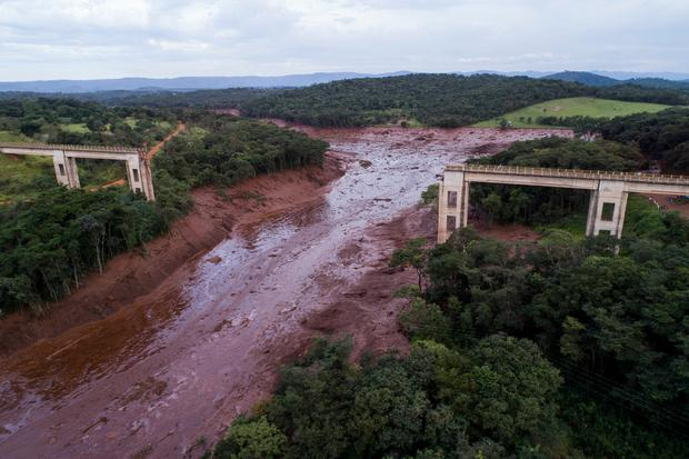 An aerial view shows a collapsed bridge caused by flooding triggered by a dam collapse near Brumadinho, Brazil, Friday, Jan. 25, 2019. The dam that held back mining waste collapsed, inundating a nearby community in reddish-brown sludge, killing at least seven people and leaving scores of others missing. (Bruno Correia/Nitro via AP)