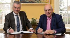 Strong ties: Patrick Prendergast and David Eastwood sign the agreement between the two universities. Photo: Fennell Photography