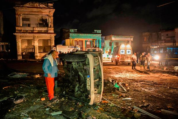 A man inspects a damaged car lying on its side in the tornado-hit Luyano neighborhood in Havana early on January 28, 2019.. (Photo by YAMIL LAGE / AFP)YAMIL LAGE/AFP/Getty Images