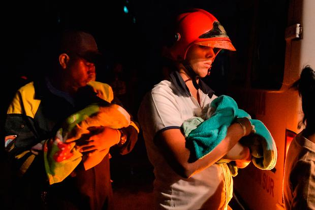 Cuban firefighters hold babies wrapped in blankets during evacuations in the tornado-hit Luyano neighborhood in Havana early on January 28, 2019.. (Photo by YAMIL LAGE / AFP)YAMIL LAGE/AFP/Getty Images
