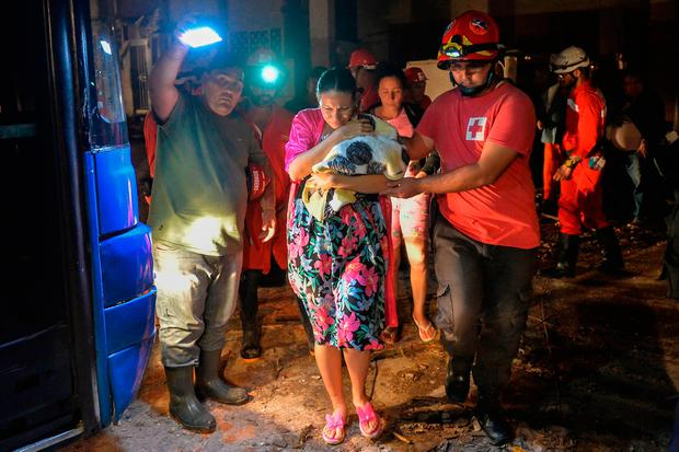 Cuban firefighters assist the evacuation of a mother and her baby in the tornado-hit Luyano neighborhood in Havana early on January 28, 2019 (Photo by YAMIL LAGE / AFP)YAMIL LAGE/AFP/Getty Images