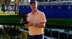 Justin Rose holds the trophy after winning the Farmers Insurance Open