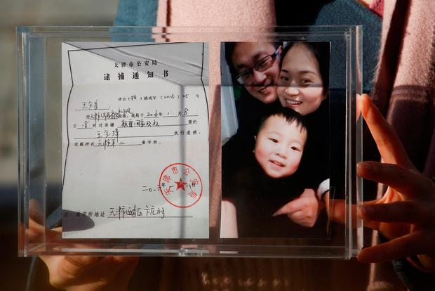 Li Wenzu, the wife of prominent Chinese rights lawyer Wang Quanzhang, holds a box with a family picture and the detention notice for her husband in Beijing, China. Photo: REUTERS/Thomas Peter