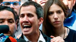 Support: Venezuelan opposition leader Juan Guaido, accompanied by his wife Fabiana Rosales, speaks to the media in Caracas. Photo: REUTERS/Carlos Garcia Rawlins