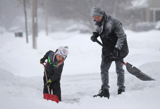 David Liebhard gets a little help from his son Levi, 4, as the two shovel their driveway Monday, Jan. 28, 2019, in Appleton, Wis. Heavy snow and gusting winds created blizzard-like conditions Monday across the Upper Midwest, prompting officials to close hundreds of schools, courthouses and businesses, and ground air travel. (Dan Powers/The Post-Crescent via AP)
