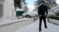 Mairtín Doherty clears snow from his home in Charlestown, Co Mayo, after a heavy fall overnight. Picture: Paul Mealey