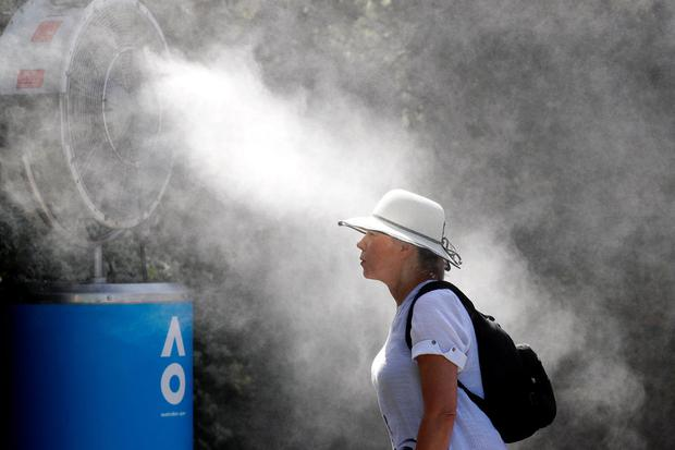 Cool down: A tennis spectator near a fan to keep cool ahead of a match at the Australian Open in Melbourne last month. Photo: Reuters/Adnan Abidi/File Photo