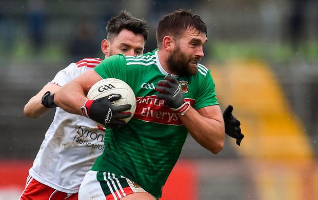 Mayo power surge: Aidan O'Shea tries to escape the clutches of Tyrone's Mattie Donnelly in Healy Park. Photo: Oliver McVeigh/Sportsfile