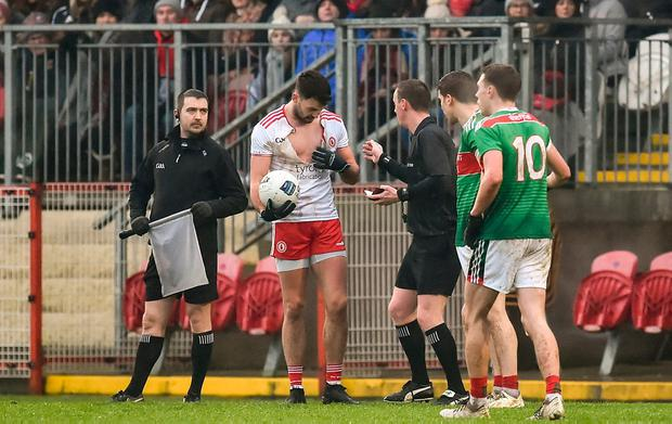 Kyle Coney of Tyrone showing his ripped shirt to referee Joe McQuillan following a second-half clash. Photo: Oliver McVeigh/Sportsfile
