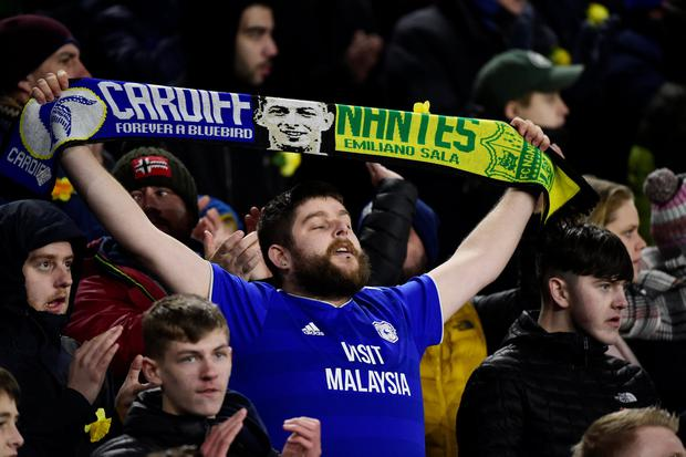 Cardiff City v AFC Bournemouth - Cardiff City Stadium, Cardiff - February 2, 2019. A Cardiff City fan holds up a scarf paying tribute to Emiliano Sala during the match REUTERS/Rebecca Naden