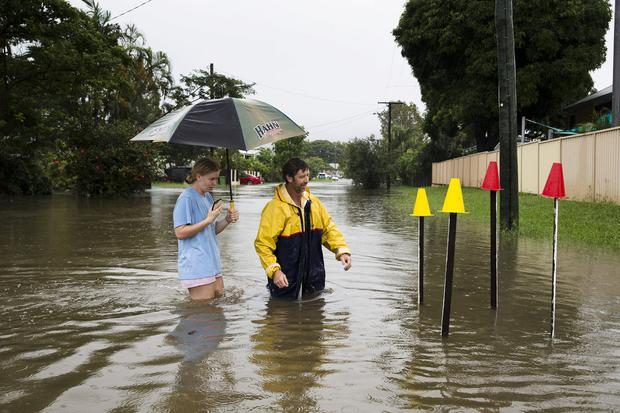 Local resident Paul Shafer and his daughter Lily stand in floodwaters near star pickets that show where the storm water cover has been removed in Hermit Park, Townsville, northern Queensland, Australia