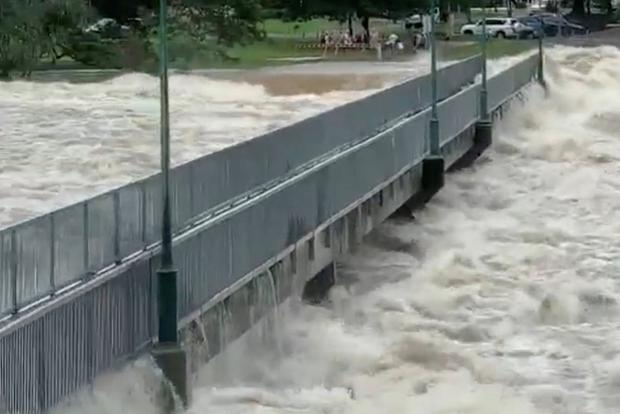 Floodwater flows by the Aplins Weir Rotary Park footbridge in Mundingburra district, Townsville, Queensland, Australia Feburary 3, 2019 in this still taken from social media video. Marissa Papageorge via REUTERS