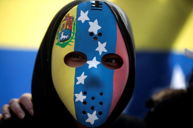 A Venezuelan living in Costa Rica wearing a mask takes part in a rally in support of Venezuela's opposition leader Juan Guaido, in San Jose, Costa Rica February 2, 2019. REUTERS/Juan Carlos Ulate