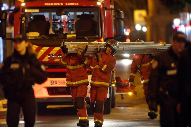 Firefighters leave the scene of a fire in Paris, Tuesday, Feb. 5, 2019. (AP Photo/Christophe Ena)