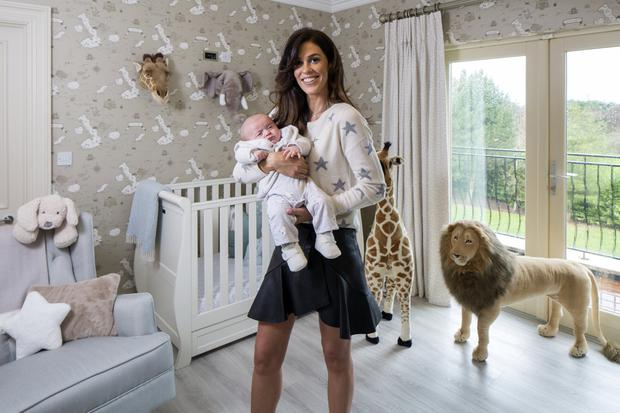 Glenda with baby Bobby in the nursery, which was designed and furnished by Arlene McIntyre of Ventura Design. Instead of opting for the obvious blue, Arlene decorated the room in restful, neutral tones. The furniture was all made by Ventura. The animals' heads are a particularly fun touch. Photo: Tony Gavin